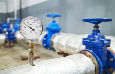 Closeup of manometer, pipes and faucet valves of water pump station system
