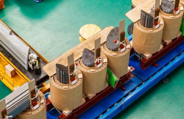 Internal active parts (core and coils) of three phase distribution oil immersed transformer during in production line